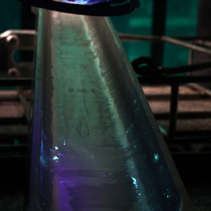 After immersion in a fluorescent dye, a component is inspected under ultraviolet light to assess the surface for imperfections.